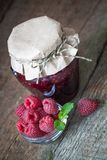 Raspberry jam with fresh raspberries. On the old wooden background Stock Images