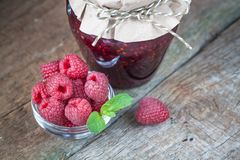 Raspberry jam with fresh raspberries. On the old wooden background Stock Photography