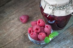Raspberry jam with fresh raspberries. On the old wooden background Royalty Free Stock Image