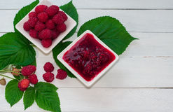 Raspberry jam and fresh raspberries ripe in the saucer. White wooden background Stock Photo