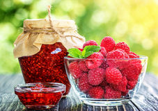 Raspberry jam  and fresh raspberry. On a rustic wooden table outdoors Royalty Free Stock Photos
