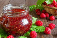 Raspberry jam and fresh raspberry in a wicker bowl on rustic wooden background Stock Image