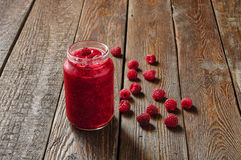 Raspberry jam in glass jar with berry on rustic wood table Royalty Free Stock Photos