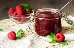 Raspberry jam in a glass jar with fresh raspberry berries. Rustic Royalty Free Stock Photo