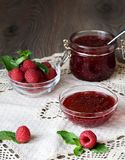 Raspberry jam in a glass jar with fresh raspberry berries.  Royalty Free Stock Images