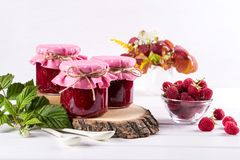 Raspberry jam in glass jar, fresh  ripe raspberry and green leaves. On white wooden table Stock Photography