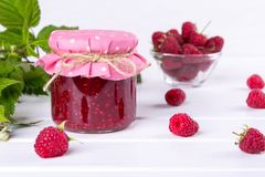 Raspberry jam in glass jar, fresh ripe raspberry and green leaves. On white wooden table Royalty Free Stock Photography