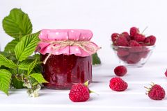 Raspberry jam in glass jar, fresh  ripe raspberry and green leaves. On white wooden table Stock Photos