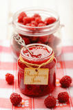 Raspberry jam in glass jar and raspberries. Selective focus. Royalty Free Stock Images