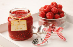 Raspberry jam in glass jar and raspberries. On white background Royalty Free Stock Images