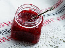 Raspberry jam in a glass jar. With a spoon on a light background Royalty Free Stock Image