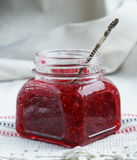 Raspberry jam in a glass jar. On white background Royalty Free Stock Photo