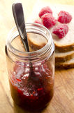 Raspberry jam in a glass with a spoon Royalty Free Stock Photography