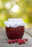 Raspberry jam. In a jar and fresh berries on the wooden table Stock Photo