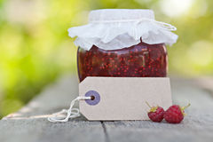 Raspberry jam. In a jar and fresh berries on the wooden table Royalty Free Stock Image