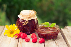 Raspberry jam in a jar and fresh berries on the wooden table. Raspberry jam ( marmalade ) in a jar and fresh raspberry on a rustic wooden table.Selective focus Stock Photography