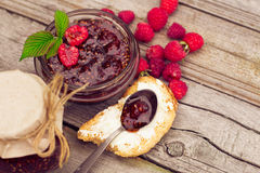 Raspberry jam in a jar and fresh berries on the wooden table Stock Photography