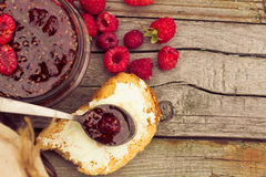 Raspberry jam in a jar and fresh berries on the wooden table Royalty Free Stock Images