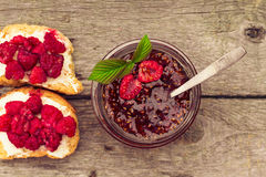Raspberry jam in a jar and fresh berries on the wooden table Royalty Free Stock Photo
