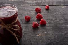 Raspberry jam in a jar on the table. Raspberry jam in a jar on the wooden table Stock Photography