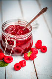 Raspberry jam in a jar on wooden background Royalty Free Stock Photos