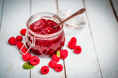 Raspberry jam in a jar on wooden background Stock Image