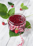 Raspberry jam in a jar on the wooden table. Raspberry jam in a jar and fresh berries on light background Royalty Free Stock Images