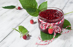 Raspberry jam in a jar on the wooden table. Raspberry jam in a jar and fresh berries on light background Stock Image