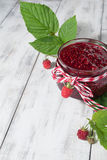 Raspberry jam in a jar on the wooden table. Raspberry jam in a jar and fresh berries on light background Stock Photography