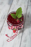 Raspberry jam in a jar on the wooden table. Raspberry jam in a jar and fresh berries on light background Royalty Free Stock Photo
