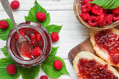 Raspberry jam and sandwiches with fresh raspberries in wicker bowl. On white wooden table. top view Stock Photography