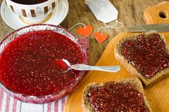 Raspberry jam and a slice of black bread Stock Images