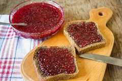 Raspberry jam and a slice of black bread Royalty Free Stock Photos
