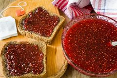 Raspberry jam and a slice of black bread Stock Image