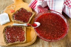 Raspberry jam and a slice of black bread Royalty Free Stock Photography