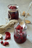 Raspberry jam on the table in banks. Raspberry jam on a black table in glass jars Royalty Free Stock Image