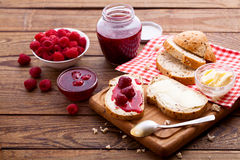 Raspberry jam to smear on wooden rustic desk. Raspberry jam to smear. Raspberry jam Bread and butter. Jars of raspberry jam with berries on tray close up Royalty Free Stock Photos