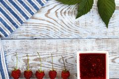 Fresh raspberry and raspberry jam on a wooden background. Berries lie in a row. Raspberry and raspberry jam on white boards Stock Image
