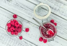 Raspberry Jam on wooden background; selective focus. Fresh made Raspberry Jam on an old and rustic wooden table; selective focus; close-up shot Royalty Free Stock Image