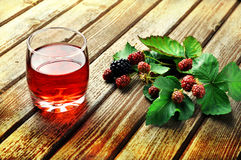 Raspberry juice. A glass of raspberry juice on a rustic table Stock Photos