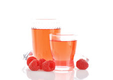 Raspberry juice and fresh raspberries. Glasses of raspberry juice and fresh raspberries on white background Stock Images