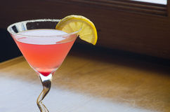 Raspberry lemon drop. On a wooden table with a lemon wedge and sugared rim royalty free stock photo
