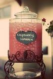 Raspberry Lemonade Drink Dispenser with love sign. Vintage Dispenser Jar on stand with Raspberry and Lemonade written on love sign Stock Photo