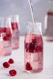Raspberry lemonade freshness of summer. Water with raspberries in a transparent glass on a vertical photo Stock Photo