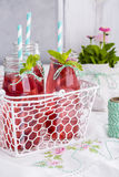 Raspberry lemonade freshness of summer. Water with raspberries in a transparent glass on a vertical photo Stock Photography