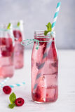 Raspberry lemonade freshness of summer. Water with raspberries in a transparent glass on a vertical photo Royalty Free Stock Photo
