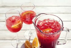 Raspberry lemonade jug with two wine glasses, orange citrus slices. wooden table background. top view. Photo Stock Photo