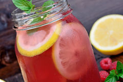 Raspberry lemonade with mint in a glass jar on table. Raspberry lemonade with mint in a glass jar on wooden table Royalty Free Stock Photography