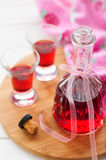 Raspberry Liqueur. A Bottle and Two Shots of Homemade Raspberry Liqueur, copy space for your text royalty free stock image