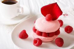 Raspberry macaroon with fresh berries and a cup of coffee close-. Raspberry macaroon with fresh berries and a cup of black coffee close-up on the table Stock Photography